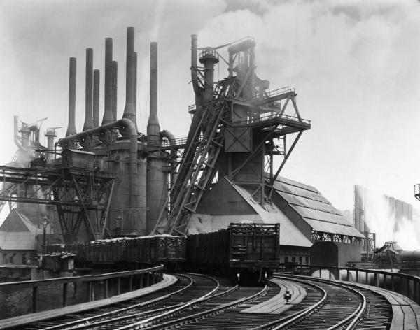 Blast furnaces of the Carnegie Steel Corporation in Pittsburgh, Pennsylvania. Photograph shows an exterior of Steel Plant with smoke stacks and railroad tracks. Undated Photograph.