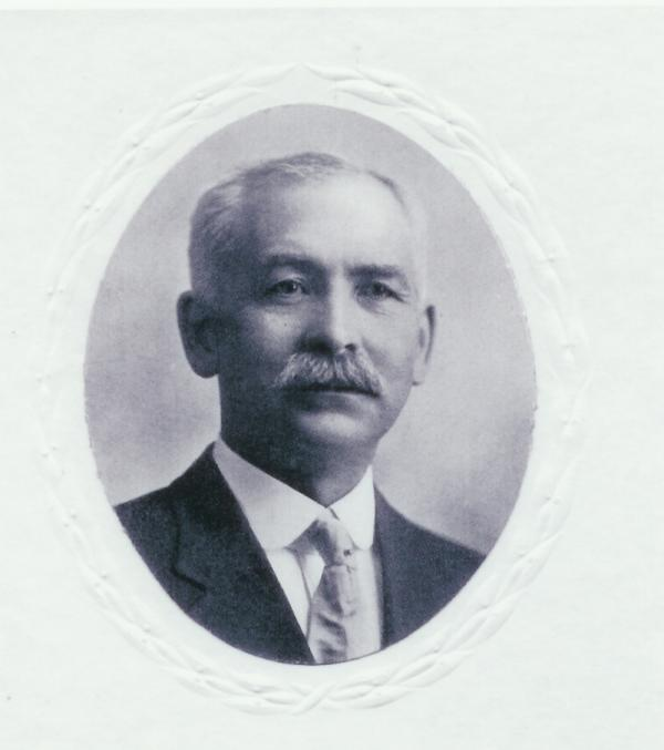 Formal Portrait of a headshot of Dietrick Lamade, sporting a mustache, wearing a suit and tie.