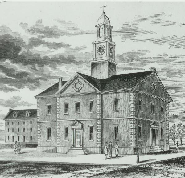 Black and white image of the Old courthouse and three men standing in front of the building.