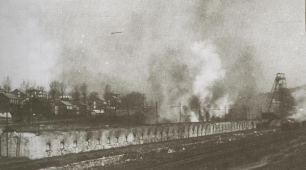 Coke Ovens and a tipple sit in the foreground of this black and white image and company houses can be seen in the background.
