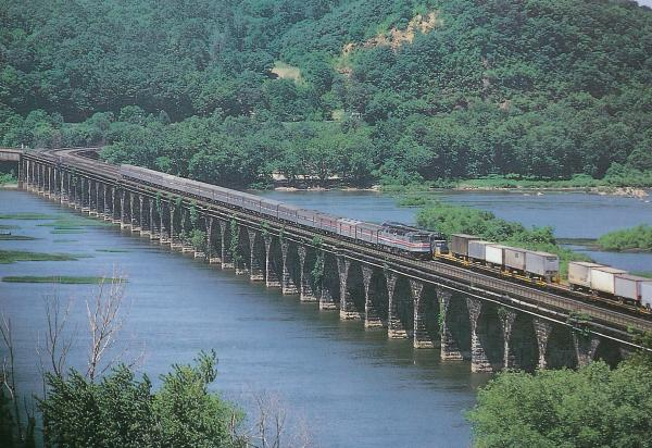 Color photograph of a train passing over the Rockville bridge.