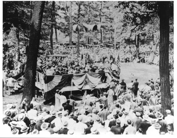 Candidate William McKinley speaks at Williams Grove on his presidential campaign trail, c.1900 from a flag draped stand while onlookers are standing below.