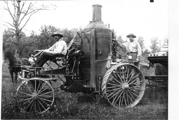 Image of threshing machine. A farmer sits on a carriage style seat. The machine has four big wheels on the sides, and an engine attached to the back with a stack extending from the base. Another farmer rides on the back. In the background sits a farmer in a carriage, drawn by a horse.