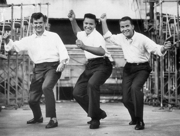 Chubby Checker leads Conway Twitty and Dick Clark through the dance the Twist.