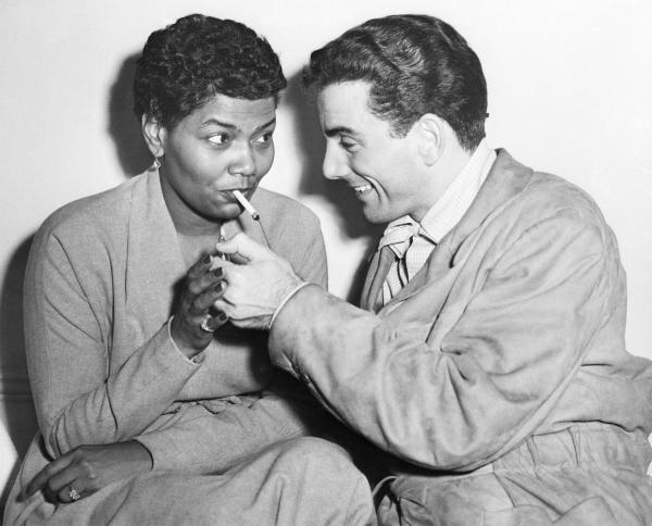 Drummer Louis Bellson Lighting Pearl Bailey's cigarette.