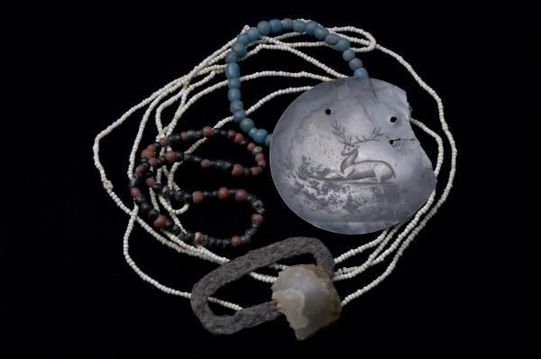 Strings of glass beads, a silver ornament with an engraved deer, and a fire starter set consisting of an English flint and iron striker, illustrate the Delaware (Lenape) Indians' dependence on trade during the 1700s.  These are among the many items collected at the Kuskuskies Town site, Lawrence County, during a 1960 archaeological investigation.