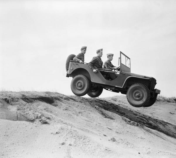 Image of a jeep and riders bouncing over rough terrain.