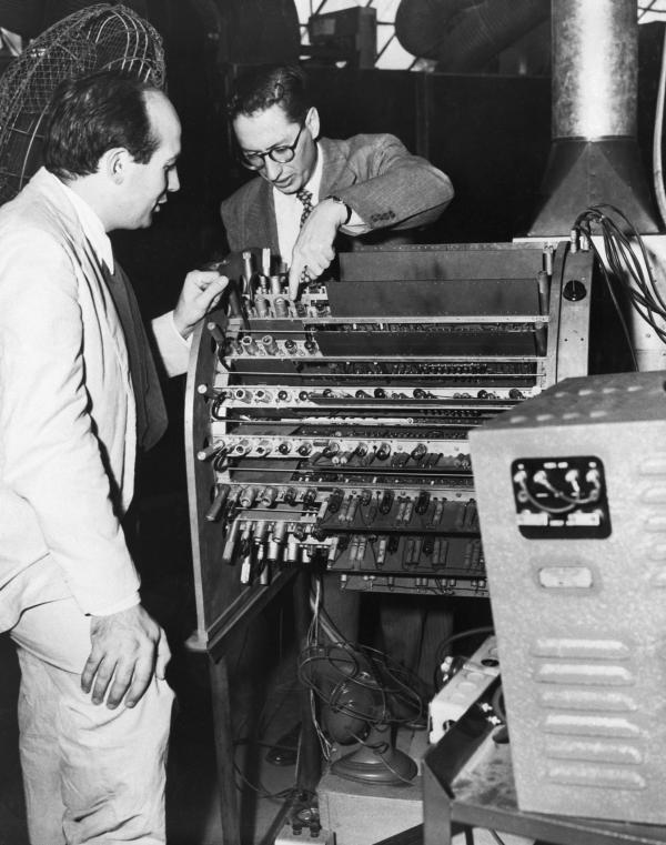 "J. Presper Eckert, Jr., co-designer and James R. Weiner, chief engineer, look over the new portable ""electronic brain."""