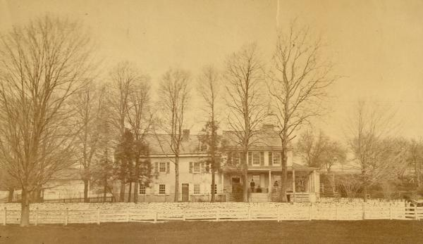 Image of the Mansion. A white, wood rail fence spreads the length of the property.
