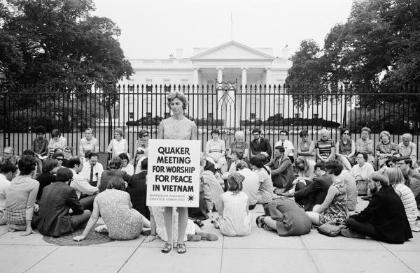 "A group of people seated on the sidewalk outside the iron fence at the White House. One woman is standing, holding a sign that reads ""Quaker Meeting for worship for peace in Vietnam."""