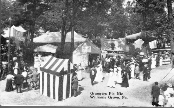 Many solid and striped tents, and the grounds are filled with fairgoers.