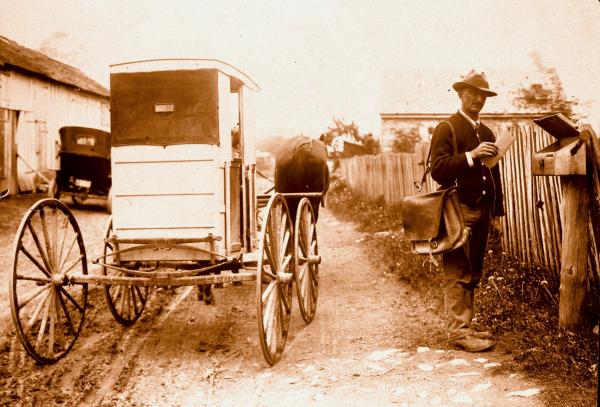 Horse and mail wagon are parked by rural mailbox as the mailman poses with satchel on shoulder and letter in hand