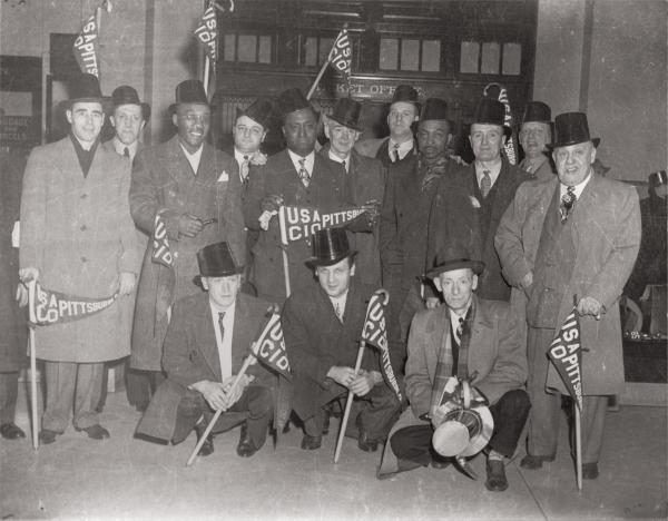 Men posing for a group portrait in front of the City County Building's ticket Office, Downtown Pittsburgh. They are wearing suits with overcoats and decorative top hats. Each is holding a cane with a USA CIO Pittsburgh flag attached.