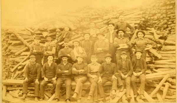 Men sitting on stack of Pig Iron, ca. 1885.
