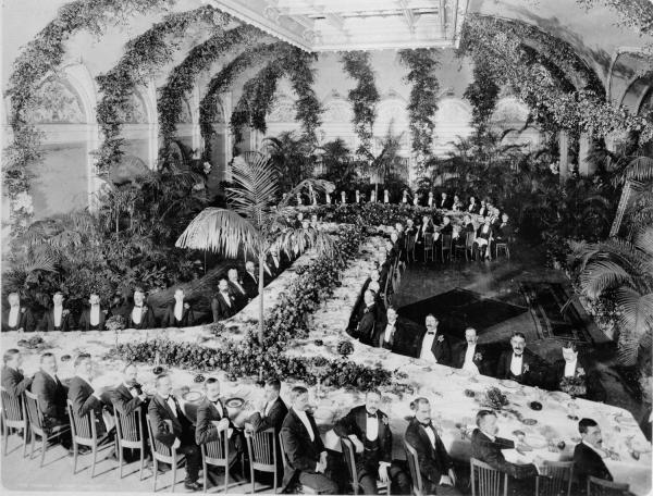 Photograph of officials from the Carnegie Companies, gathered together in a lavish ballroom.