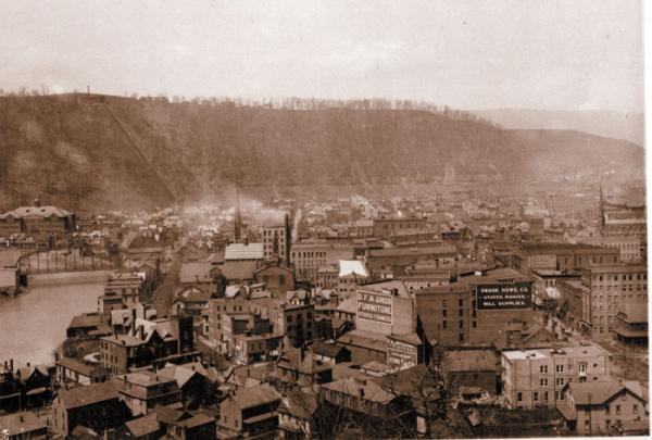 Black and white photograph of the view of downtown Johnstown Stoneycreek River on left of photo.
