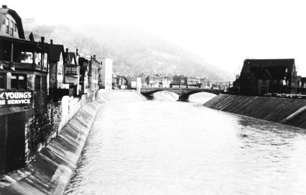 Black and white photograph of town and flood walls.
