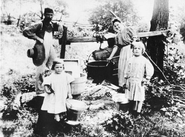 Black and white image of man and woman with two young girls preparing for wash day on the farm. A big black kettle hanging over an open fire holds the water. A wash tub sits on the ground and one can see the wash board placed inside. Buckets for carrying water are in the children's hands.