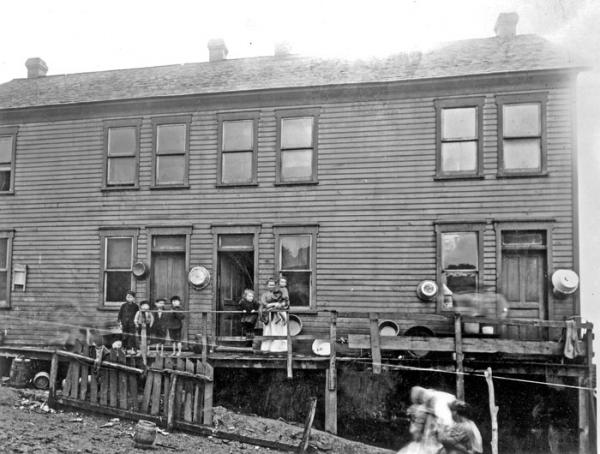 A woman and six children stand outside on a dilapidated, wooden, porch which is attached to a two-story, wooden, home.  They appear to be posing for this photograph. There are three entrances to this structure and a wash tub hanging next to each one.