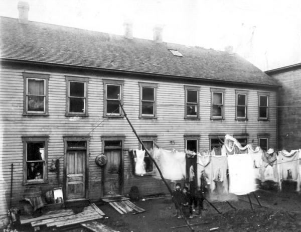 In this backyard there are several lines of laundry hanging from lines that are attached to the house and extend to poles. Several small children pose underneath one of the lines for this photograph. The house is a long, two- story, wooden, structure with eight windows across the top floor. On the bottom floor there is a window to the left and two small children peer out from the inside. To the right of this window are two doors, with a wash tub hanging between the two. To the right of the doors, five windows fill the rest of the bottom floor walls. The yard is filled with debrie.