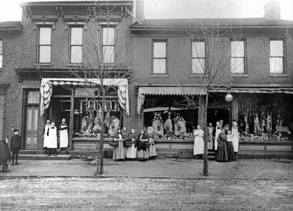 Butcher shop workers and shoppers pose outside of two Cambria City butcher shops