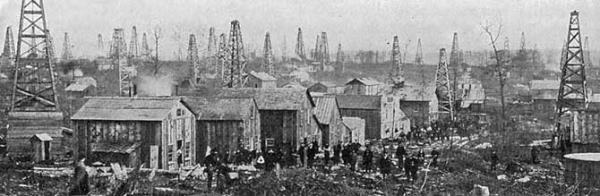 A group of hastily constructed buildings stand in a line along a primitive road in front of a field full of oil derricks.