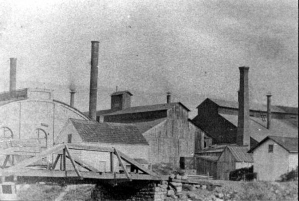 Image of the buildings, stacks, and a bridge. Bessemer buildings to left.