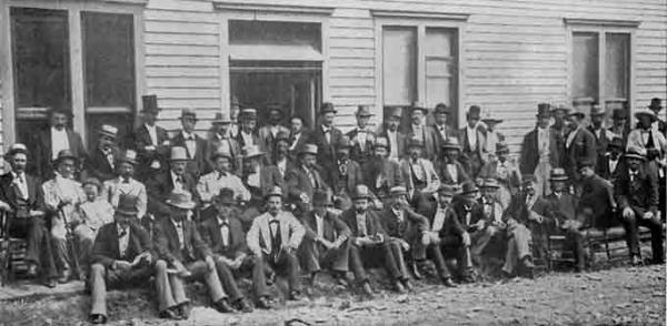 A group of several dozen formally dressed businessmen pose on a sidewalk in front of a clapboard building.