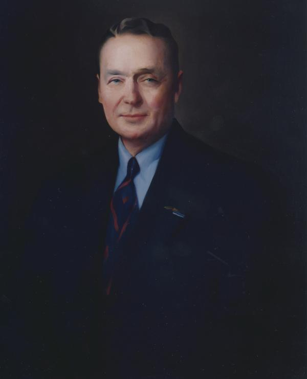 Head and shoulders portrait of Earle wearing a suit.