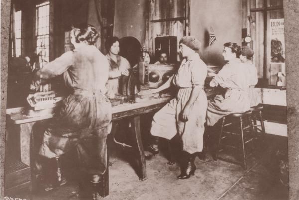 Photograph of Midvale Steel Company female workers. One woman grinds a small gear.