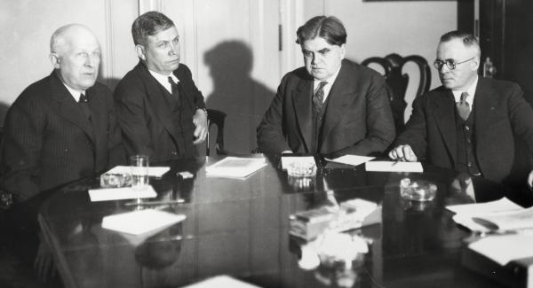 Four men, dressed in tailored suits, are gathered around a conference table. Papers sit on the table in front of each person, and a glass in front of one of the men. Several ashtrays are also on the table. John L. Lewis (2nd from the right) and UMW vice president Thomas Kennedy (far right) led an aggressive campaign to organize the Pennsylvania coal mines. (W.W. Inglis, President of the Glen Alden Coal Company, and A.J. Maloney, President of the Philadelphia and Reading Coal and Iron Company, are on the left.)