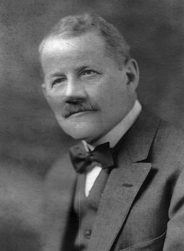 Head and shoulders photograph of Mishler wearing a vest, suit jacket, and a bow-tie.