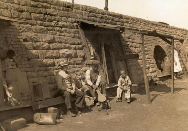 Image of two men and two children sitting outside on a bench in front of their coke oven home.