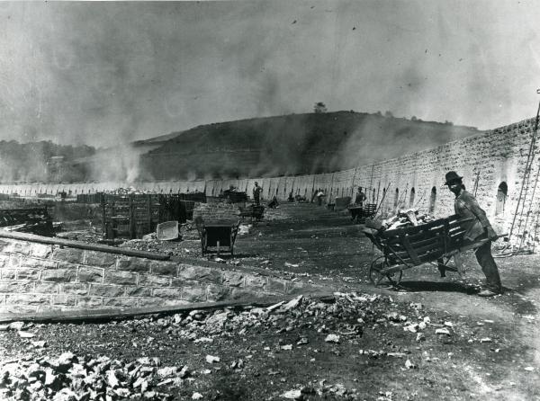 Black and white photograph showing a wall of coke ovens being worked and a Coke Drawer with a wooden wheelbarrow of Coke. Smoke is heavy in the air.