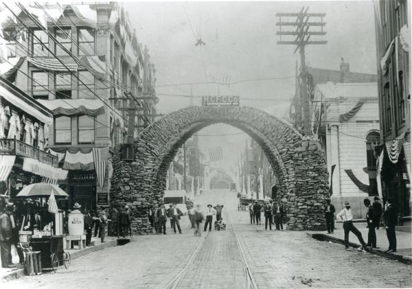 """A huge coke arch stretches across the width of a street. On the top of the arch is a sign that reads: HCFC Co. People are standing under and to either side of the arch, as well as along the city street. Directly underneath the center of the arch, a young boy kneels with his arms around his dog's neck. Banners and flags hang from the buildings. To the right of the photograph are vendors and a large barrel that reads """"ice water"""". Almost every man on the street wears a suit and a hat. In the background of the image, on the opposite side of the arch one can see two wagons and horses harnessed."""