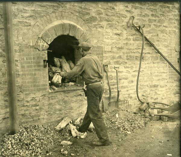 Black and white photograph of worker withdrawing coke from an oven. Working is wear a cap, long-sleeved shirt, and pants, with a tool belt. Some industry tools can be seen leaning on the oven wall off to the right of the worker.