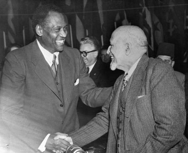 """Paul Robeson, American singer, is shown (left) as he was congratulated by Dr. William E.B. Dubois, American editor and Author, after Robeson addressed the red-sponsored world """"Peace"""" conference in Paris."""