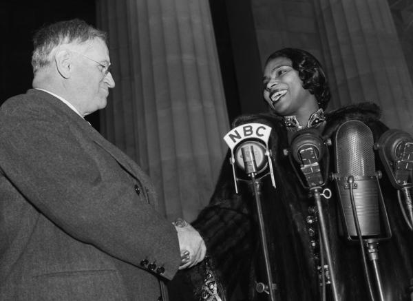 Secretary of the Interior Harold Ickes congratulates Miss Marian Anderson from the steps of the Lincoln Memorial.
