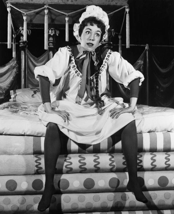 Carol Burnett dressed as Princess Winnifred in her bed clothes, sits on the end of a Mattress.