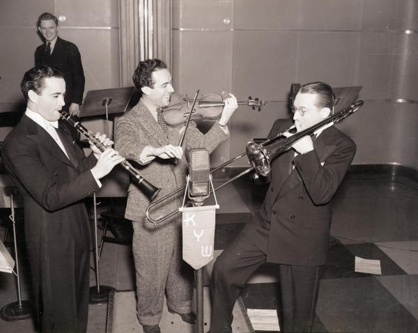 "Noted orchestra leaders Buddy Rogers; Jan Savitt of KYW; and Tommy Dorsey (L-R) are pictured as putting on an impromtu ""swing"" show for studio technicians and musicians."