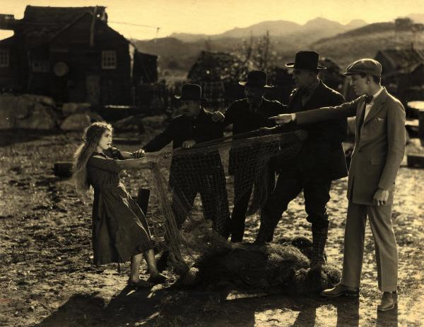 Three men attempt to pull a net from the hands of a young woman, while another man points at her defiantly.