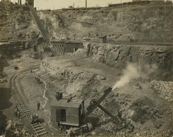 Several miners in ore pit with mining equipment. Photograph shows railroad tracks and steep inclined plane in background used to transport the ore out of the pit.