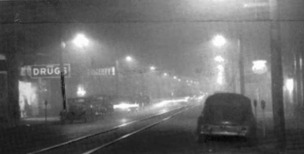 Streetlights pierce a dense fog that is so thick, it looks like nightfall on a city street.