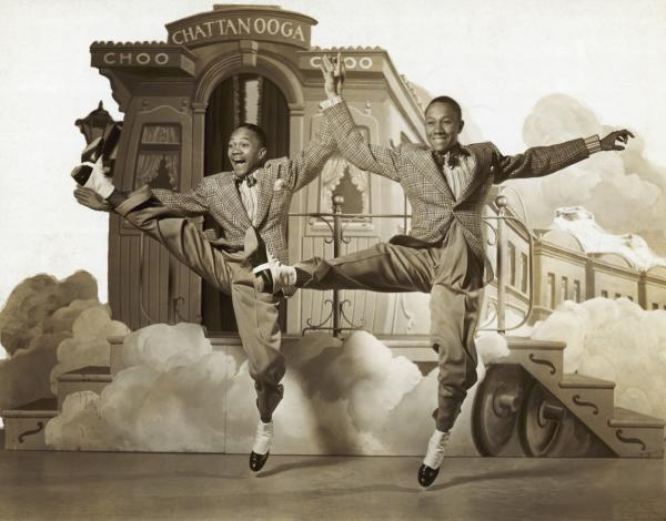 Image of the Nicolas brothers dancing on a the stage of  a set.