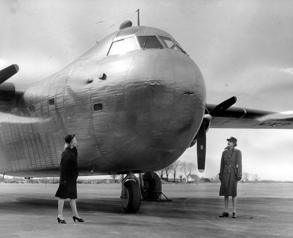 WAVE Sally Siebert from Pittsburgh and WAC Winifred Thompson inspect nose of the first large size cargo airplane constructed of stainless steel. WAVES and WACS stand near the huge tail at Budd Field, Red Lion Road and Reveree Road.   January 29, 1945.