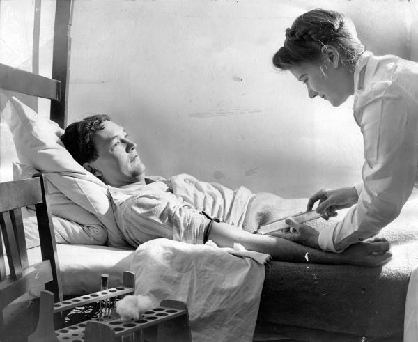 Former Yale Law School student who opposed the war, contracted hepatitis for the sake of science, bares his arm for the nurse's blood taking needle.
