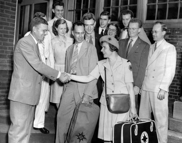 Photograph of a group of well dressed people, one woman carrying a suit case shakes the hand of a gentleman.