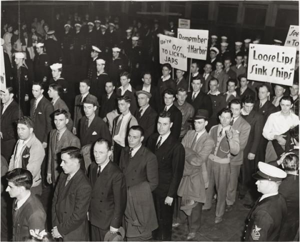 Rows of men waiting in lines to enlist.Some carry signs, which read Loose lips sink ships and other slogans.