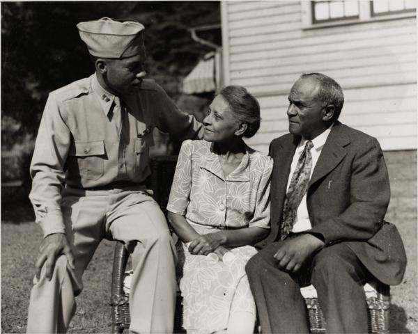 Wiley, in uniform, sits on the arm of a bench while his parents sit on the seat.
