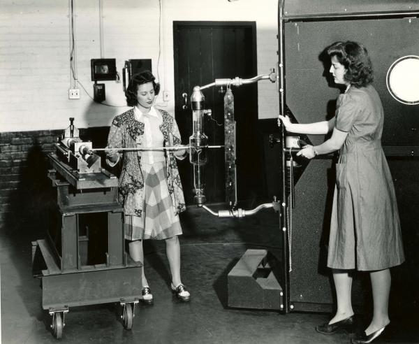 Two women pose with machinery for publicity photograph.